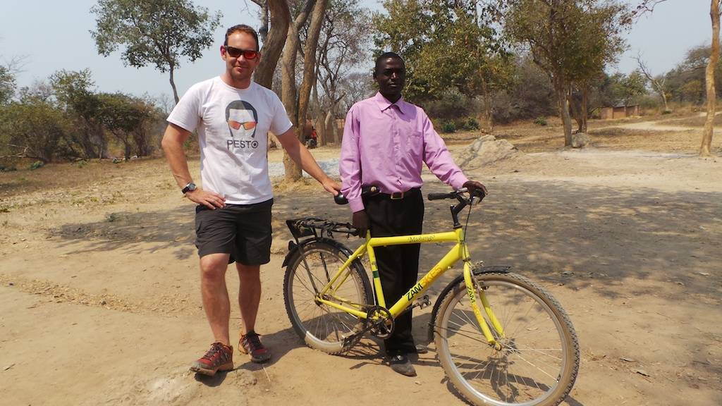 Mr. Lifumpa, the teacher, with Tim Pestridge and the bike donated by the Monday Knights.